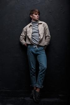 Modischer attraktiver junger mann in einer weißen kühlen jacke in stilvollen blauen modischen jeans in grauem golf in schwarzen turnschuhen, die drinnen nahe einer grauen wand aufwerfen. stilvolles kerlmodell. moderne herrenmode