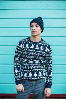 Modischer attraktiver junger mann mit blauen augen in einem vintagen hut in einem blauen weihnachtsstrickpullover in jeans steht in der stadt an der wand einer hellblauen holzwand. netter kerl.