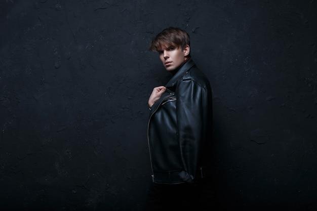 Modischer cooler junger mann mit einer frisur in einer schwarzen lederjacke im retro-stil mit schwarzen jeans, die in einem dunklen raum nahe der schwarzen wand stehen und in die kamera schauen. netter stylischer typ.