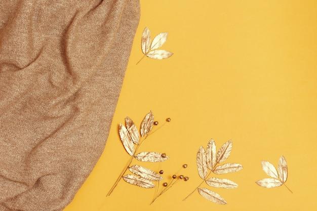 Modischer gestrickter schal und goldenes herbstlaub auf gelbem papier