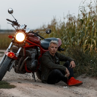 Modischer gutaussehender brutaler mann in einer khaki-jacke sitzt in der nähe eines motorrads auf dem feld