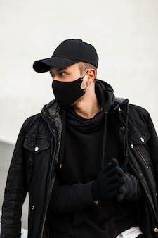 Modischer, gutaussehender junger mann mit einer schwarzen mockup-designkappe mit schutzmaske in einem schwarzen hoodie mit jacke und handschuhen auf der straße