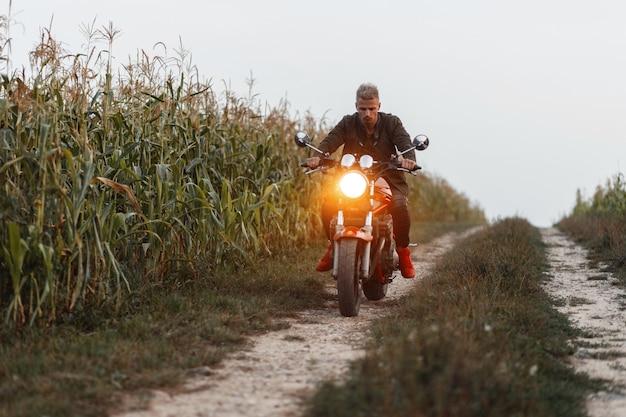 Modischer gutaussehender mannreisender, der ein motorrad mit licht in einem feld mit mais reitet