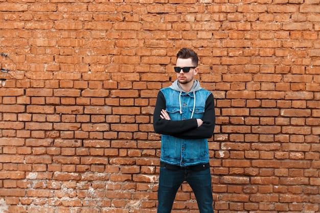 Modischer hipster-mann in der jeanskleidung mit sonnenbrille nahe einer mauer