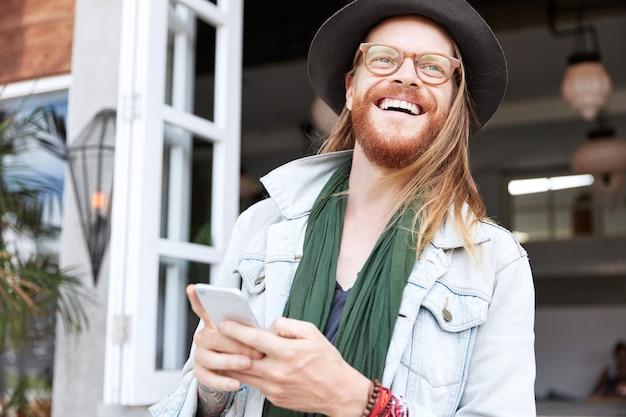 Modischer hipster-typ, gekleidet in stilvollen schwarzen hut und jeanshemd