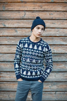 Modischer hübscher junger mann in der stilvollen jeans in einer strickmütze in einem festlichen blauen pullover der weinlese mit einem weißen muster auf einer hölzernen vintage wand der wand. attraktiver typ.