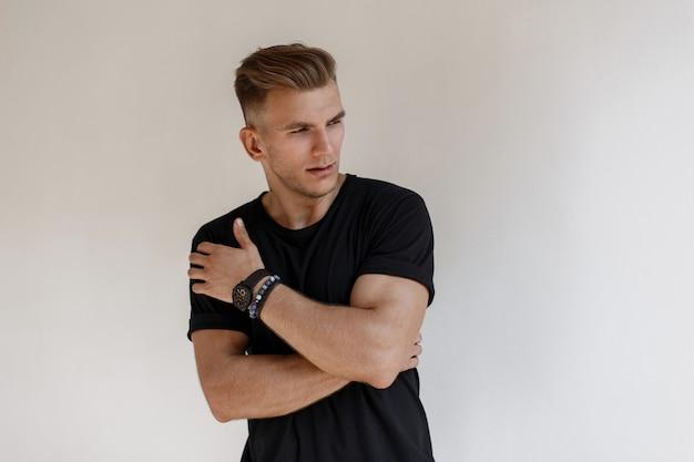 Modischer hübscher junger mann mit frisur in einem schwarzen t-shirt mit einer uhr wirft nahe einer weißen wand auf der straße auf
