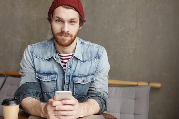 Modischer junger bärtiger mann in hut und jeanshemd, der am kaffeetisch mit pappbecher frischem kaffee sitzt, handy hält, während er online nachrichten sendet und im internet surft, unter verwendung von kostenlosem wi-fi