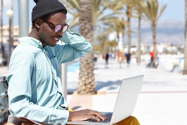 Modischer junger freiberufler, der stilvolle kleidung und accessoires trägt, die auf bank sitzen