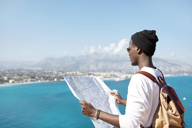 Modischer junger männlicher rucksacktourist, der papierkarte hält und oben auf berg über ozean steht,