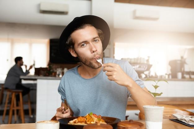 Modischer junger mann, der leckeres essen zum mittagessen genießt, das am holztisch des gemütlichen restaurants sitzt. hungriger hipster, der einen trendigen schwarzen hut trägt, der seinen hunger stillt, während er allein in der cafeteria isst