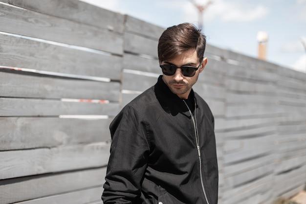 Modischer junger mann in einer schwarzen jacke mit dunkler sonnenbrille genießt einen spaziergang auf der straße an einem sonnigen sommertag. amerikanischer stilvoller kerl entspannt sich nahe einem weinlese-holzzaun im freien.