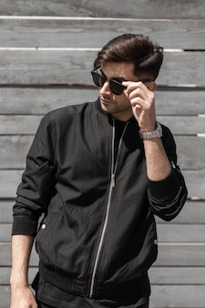 Modischer junger mann in einer schwarzen weinlesejacke in der schwarzen dunklen sonnenbrille mit der trendigen frisur stellt nahe einer weinlesewand der bretter an einem sonnigen tag auf. attraktiver typ entspannt sich in der sonne. herrenbekleidung.