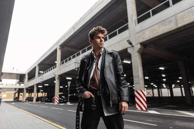 Modischer junger mann in einer trendigen schwarzen lederjacke in einem hemd in hosen mit einem stylischen rucksack mit einem frisurenstand in der nähe der straße in der stadt. cooles modernes kerlmodemodell in der freizeitkleidung der jugend.