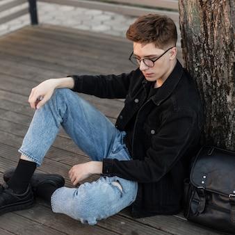 Modischer junger mann in vintage-brille in trendiger denim-freizeitkleidung in turnschuhen mit lederrucksack