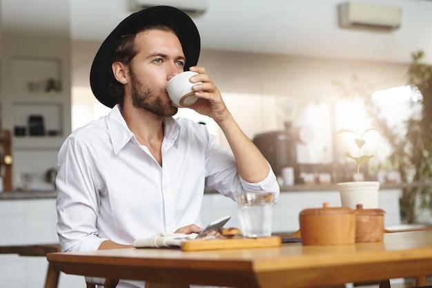 Modischer junger mann mit bart, der hut und weißes hemd trägt, das heißes getränk hat, am tisch sitzt und gadget in seiner hand hält. kaukasischer mann, der handy benutzt, tee oder kaffee im gemütlichen café trinkend
