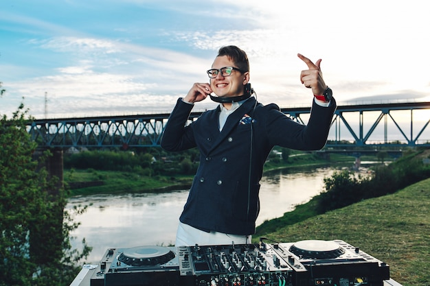 Modischer junger mann mit dj-konsole, um spaß zu haben