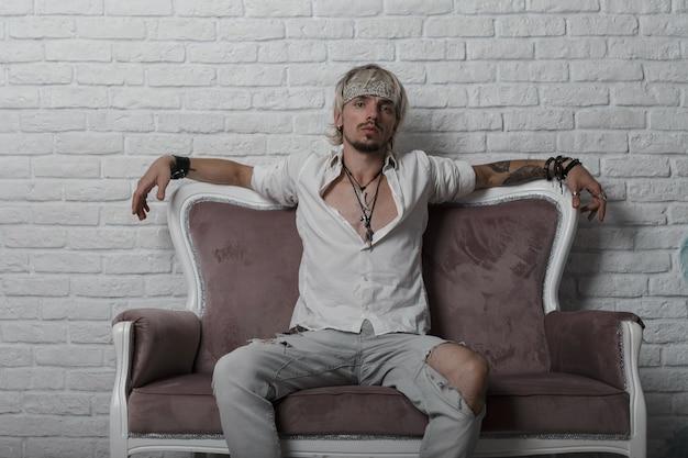 Modischer junger mann mit einer stilvollen frisur in einem trendigen kopftuch in einem weißen hemd in zerrissenen jeans