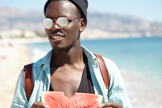 Modischer junger reisender, der scheibe der süßen reifen wassermelone hält