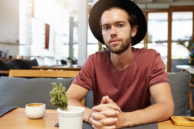 Modischer junger unternehmer, der t-shirt und trendigen schwarzen hut trägt, der am hölzernen tisch mit becher und kaktus sitzt, während cappuccino allein im café hat und auf seinen partner für treffen wartet