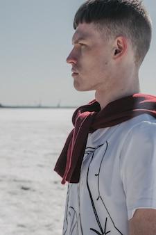 Modischer kerl, der auf dem gefrorenen seeufer im weißen t-shirt und im roten pullover über seinem hals steht.