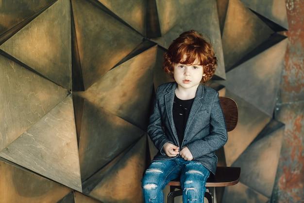 Modischer kleiner junge, der mit seinen armen gekreuzt sitzt und an der kamera lächelt. abstrakter hintergrund