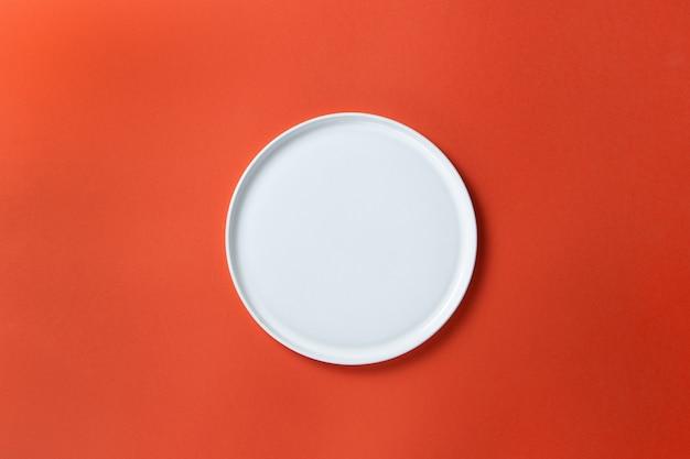 Modischer leerer weißer runder teller mit geraden kanten auf rotem papier, minimaler flacher lage, kopierraum.
