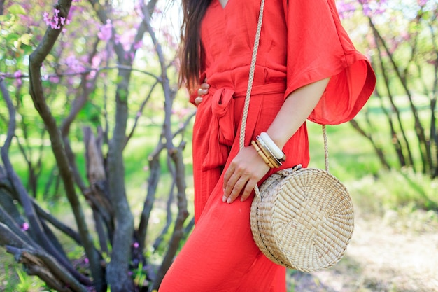 Modischer look des frühlings, frau, die stilvolle trendige böhmische bali-rattanstrohsack hält und korallenboho-kleid trägt.