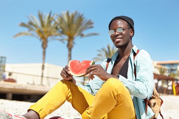 Modischer männlicher student, der reife wassermelone isst