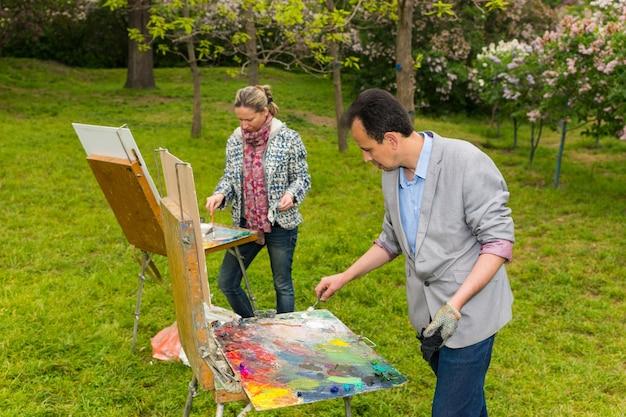 Modischer männlicher und weiblicher maler, der draußen im park oder im garten auf einem bock und einer staffelei arbeitet, die farbe mit einem spachtel während eines kunstunterrichts mischen