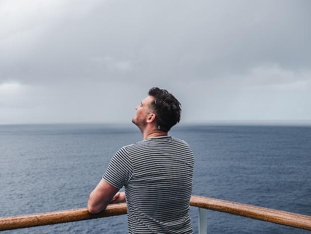 Modischer mann auf dem leeren deck eines kreuzfahrtschiffes vor dem hintergrund der meereswellen.