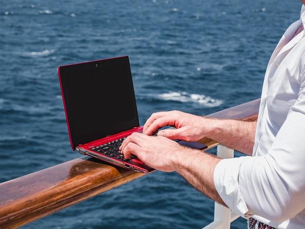 Modischer mann, der an einem roten laptop arbeitet