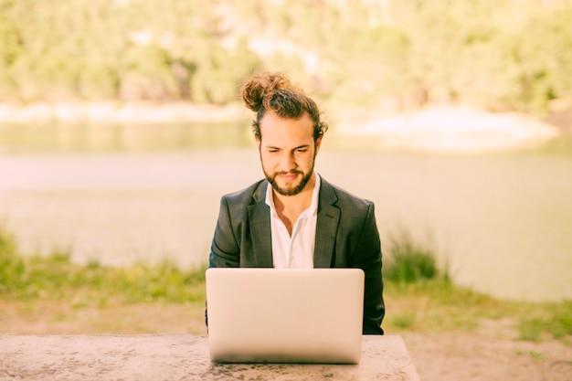 Modischer mann, der draußen mit laptop arbeitet