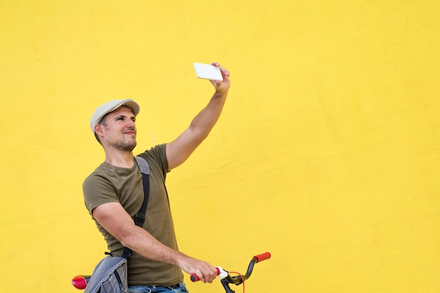 Modischer mann, der ein selfie mit seinem örtlich festgelegten fahrrad nimmt
