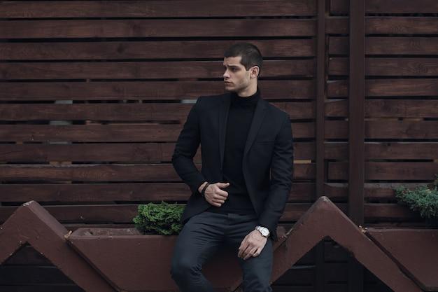 Modischer mann, der einen anzug trägt und an der holzwand sitzt