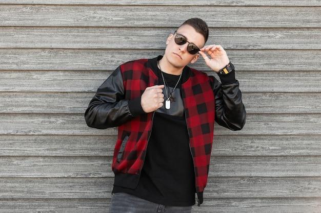 Modischer mann des amerikanischen hübschen hipsters mit stilvollem haarschnitt in der sonnenbrille in einem trendigen schwarzen t-shirt in einer karierten jacke mit amuletten um den hals nahe einer vintage holzwand
