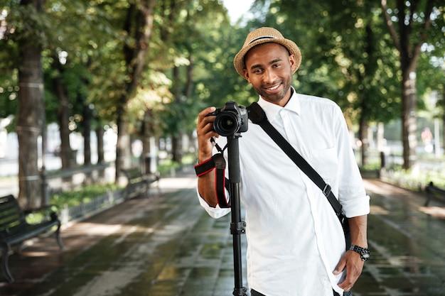 Modischer mann im park mit hut, der fotografien macht