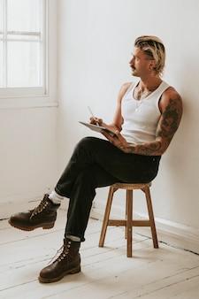 Modischer mann im weißen trägershirt unter verwendung der digitalen tablette