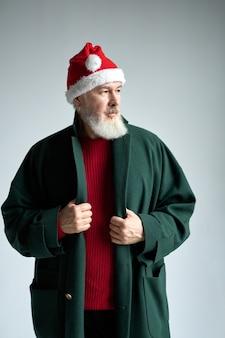 Modischer mann mittleren alters mit weihnachtsmütze, der ein stilvolles outfit trägt und beiseite schaut