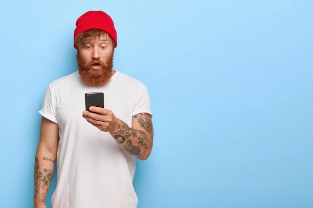 Modischer rothaariger kerl, der mit seinem telefon aufwirft