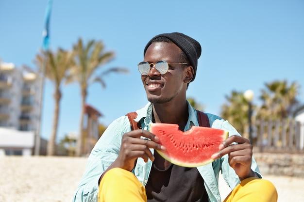 Modischer rucksacktourist, der frische saftige wassermelone isst