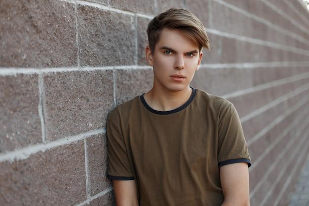 Modischer schöner junger mann mit einer stilvollen frisur in einem weinlesegrün-t-shirt, das nahe an einer weinlese-steinmauer an einem warmen sommertag ruht