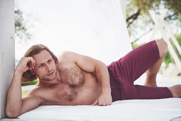 Modischer sexy perfekter mann am strand.