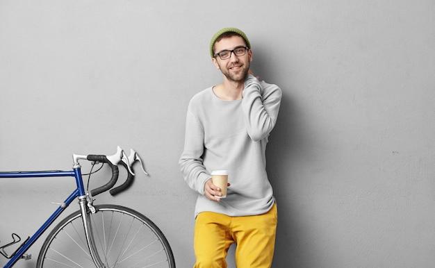 Modischer student, der nach dem unterricht mit dem fahrrad nach hause fährt, anhält, kaffee zum mitnehmen trinkt, angenehm lächelt, während er sich mit seinem alten freund trifft und ein angenehmes gespräch führt