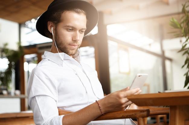 Modischer student mit weißen kopfhörern, die kostenloses wlan nutzen, um seinen freund auf seinem handy per video anzurufen und auf den bildschirm zu schauen und zu lächeln. junger hipster in der schwarzen kopfbedeckungsnachricht online