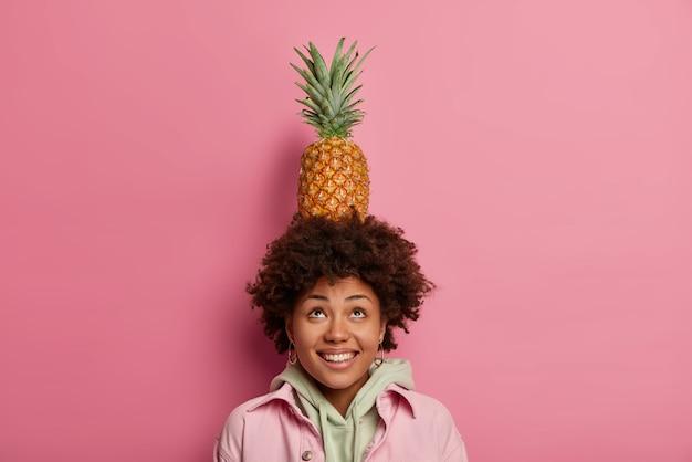 Modischer teenager hält ananas auf dem kopf, macht trick mit tropischen früchten, schaut nach oben, lächelt breit, hat weiße zähne, trägt hoodie mit jacke