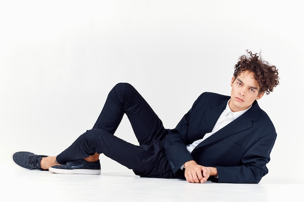 Modischer typ in anzug und turnschuhen, der auf dem boden in einem hellen raummodell für lockiges haar sitzt