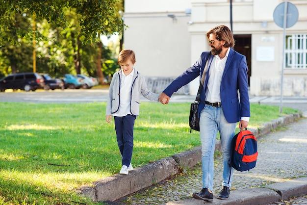 Modischer vater und sohn, die auf der straße gehen. eltern mit kind nach der schule nach hause gehen. vater und sohn halten hände im freien.
