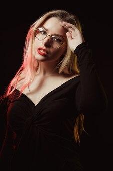 Modisches blondes model in brille mit bluse mit nackten schultern