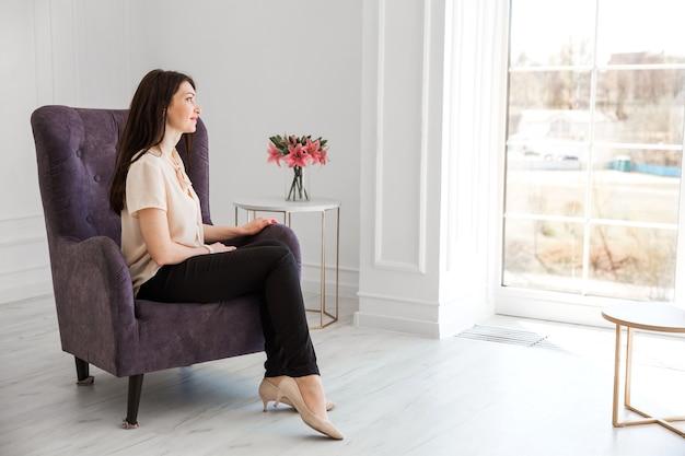 Modisches brünettes mädchen in einer hellen bluse sitzt auf einem stuhl, posiert und schaut aus dem fenster.